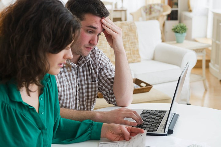 couple frowning at computer screen
