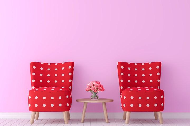 chaises rouges à taches blanches et mur rose