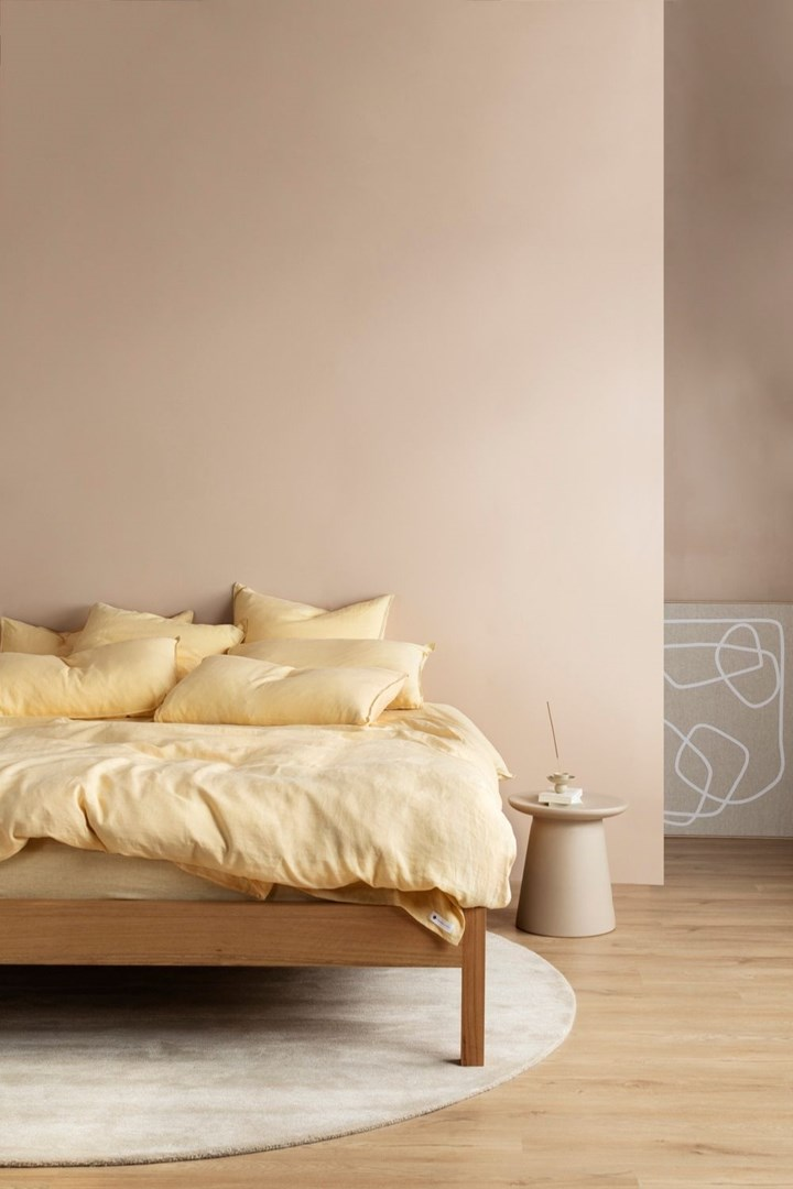 Timber bed with yellow linen in a peach-coloured room