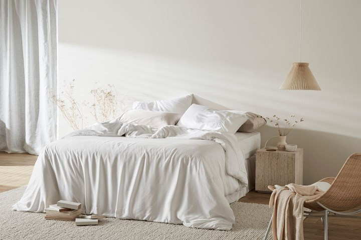 Bed made up with white and soft grey linen