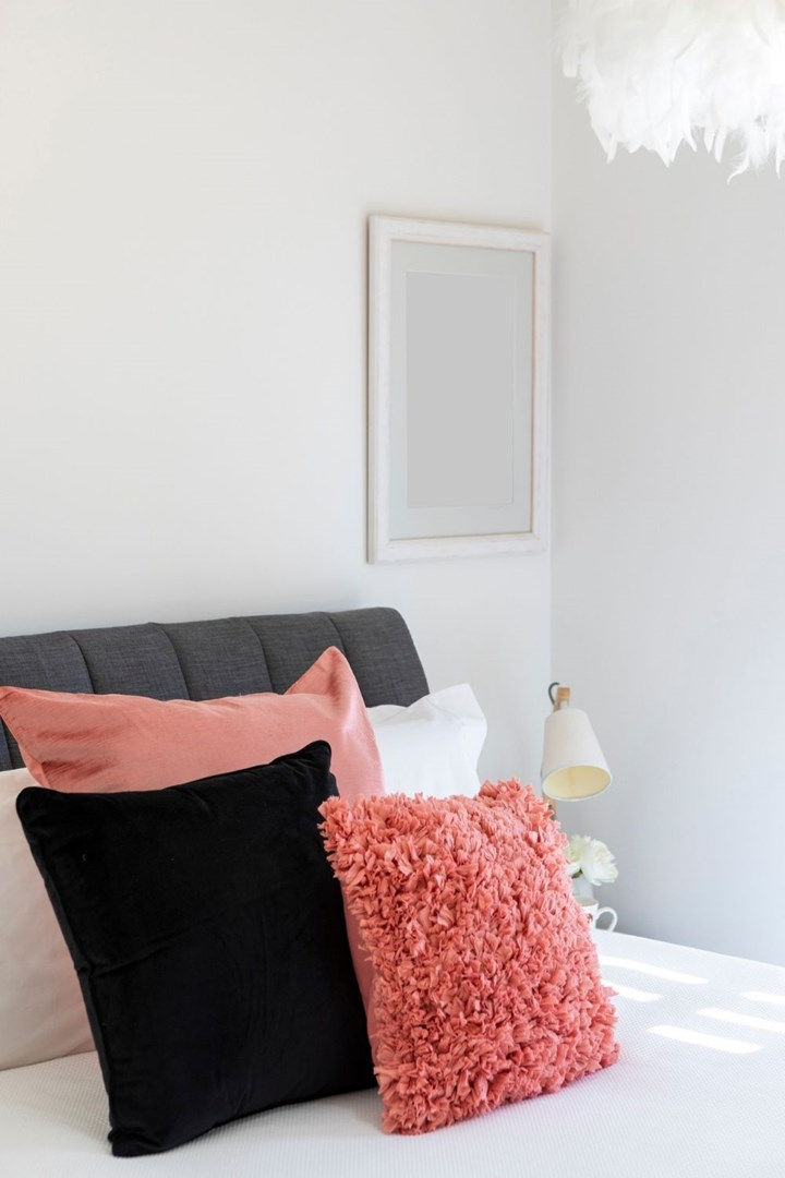 Pink cushions on bed styled with white linen