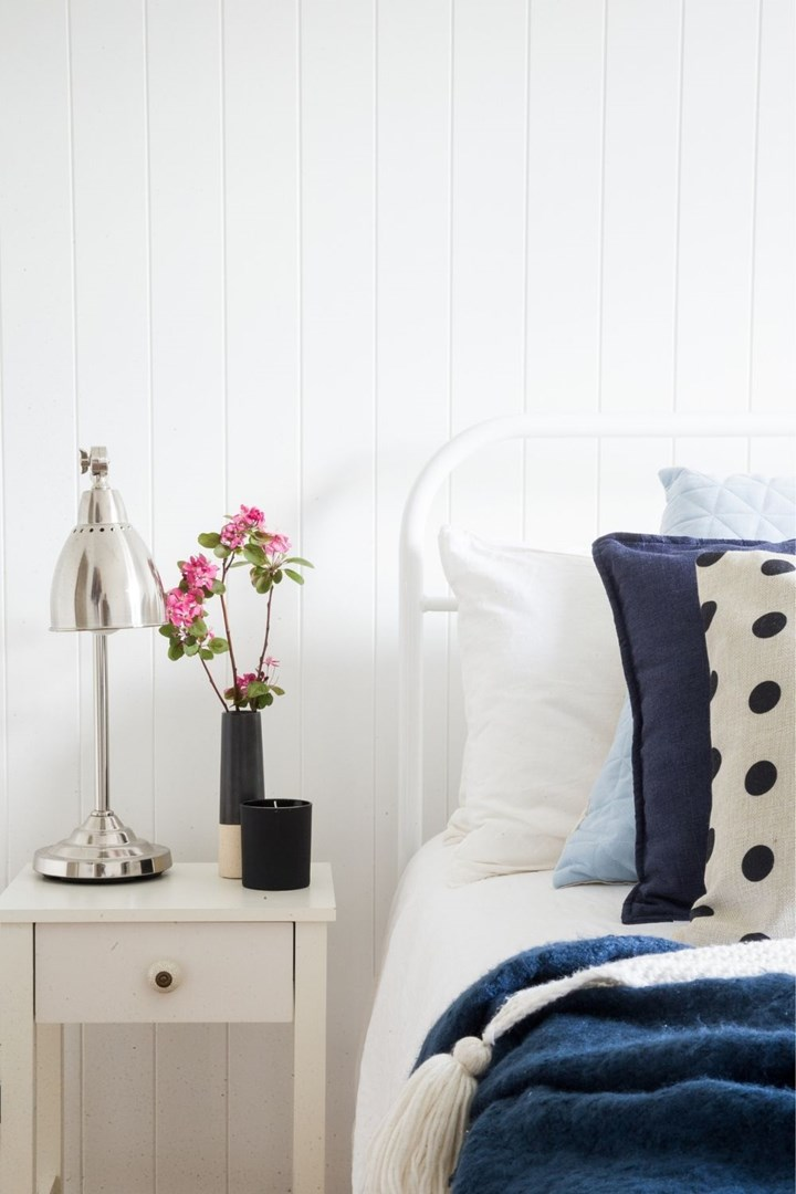 White bedroom with blue accent pieces