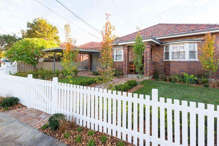 Brick house with white picket fence