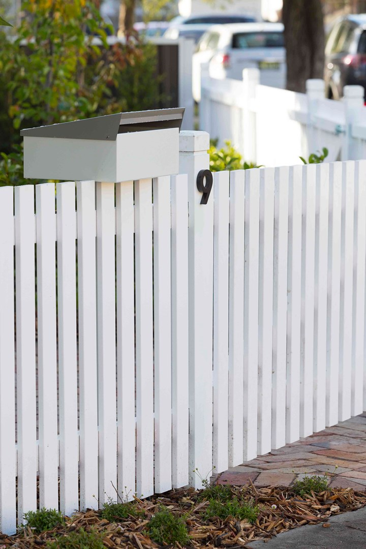 White picket fence with letterbox