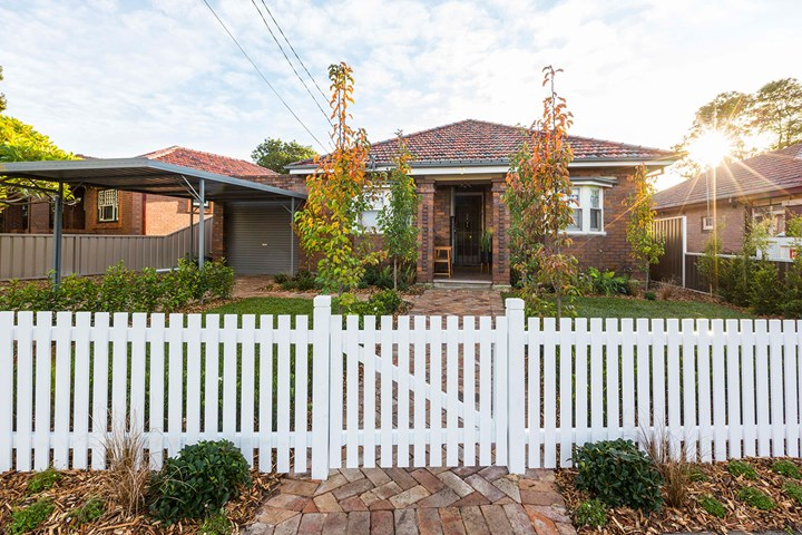Brick home with tidy front garden and white picket fence