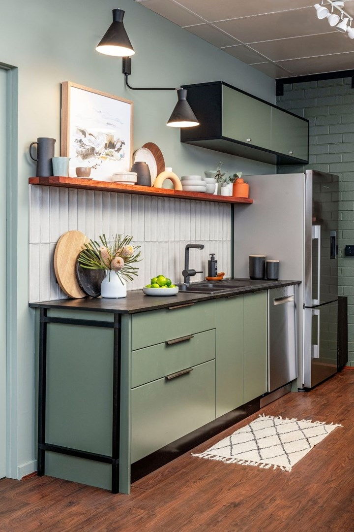 Green industrial-style kitchen with open shelving